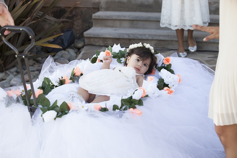 Young flower girl pulled down aisle in wagon decorated with tulle, pink rose, white rose, greenery