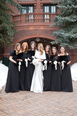 Bridesmaids in black long dresses with fur hand warmer muffs and fur wrap shawls