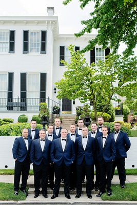 groom with groomsmen in front of wedding venue with navy tuxedo jacket black bow tie pants