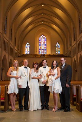 Groom with mother and father in white and family with baby