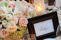 Teddy's table name next to rose centerpiece at wedding