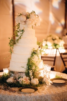 Tall six tier wedding cake round with white frosting, ivory peony flowers, greenery