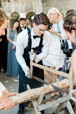 bride and groom sawing log in half after germany wedding ceremony german traditions