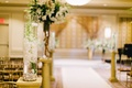 Wedding ceremony with submerged white orchid stems and floating candle on golden pedestal