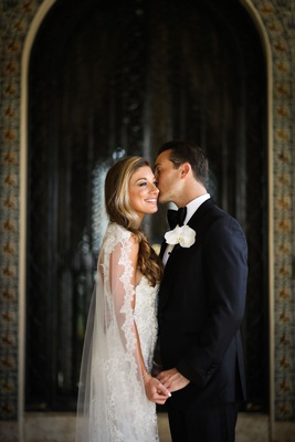 bride in monique lhuillier lace wedding dress with cape veil groom in tuxedo white boutonniere kiss