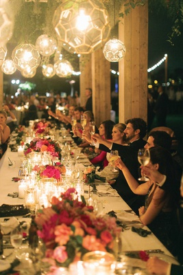wedding reception outdoor table glass orb lantern pendant lights low pink centerpiece toasts cheers