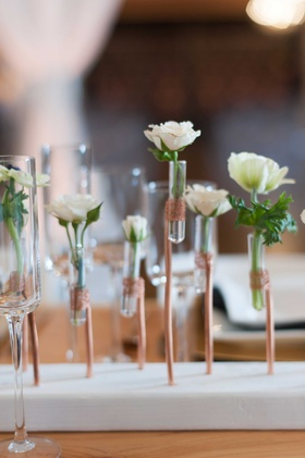 miniature white and green floral arrangements in clear tubes help up by copper wire