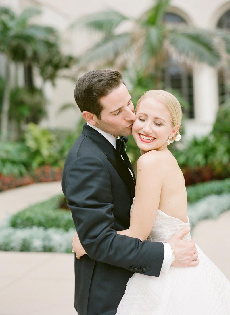Man in tuxedo kisses woman in wedding dress