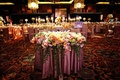 Wedding reception with a decorative table draped in a rosy tablecloth and covered with flowers
