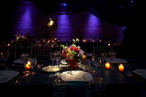 table lit by purple lighting with jewel toned flowers and candles
