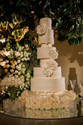 Tall white wedding cake with sugar flower peony design and invitation escort card design style