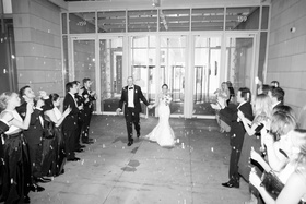 black and white photo of bride and groom make grand exit as guests blow bubbles