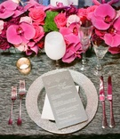 Grey reception table linen with silver charger plate, pink orchid centerpiece, white wine goblet