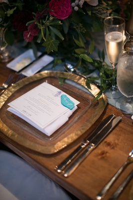 Wedding reception wood table gold charger plate blue sea glass place card greenery runner