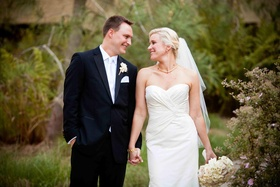 Newlyweds holding hands in garden