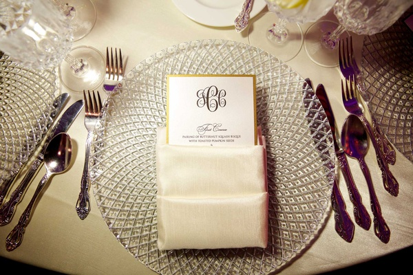 Black monogram menu card with gold border in ivory napkin on top of crystal charger plate