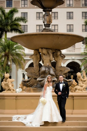 Bride in strapless wedding dress and bouquet with cathedral veil and groom in tux at The Breakers