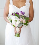 African American bride carries white and purple bouquet