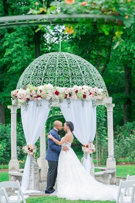 bride and groom at gazebo as altar with blush and marsala roses, drapery