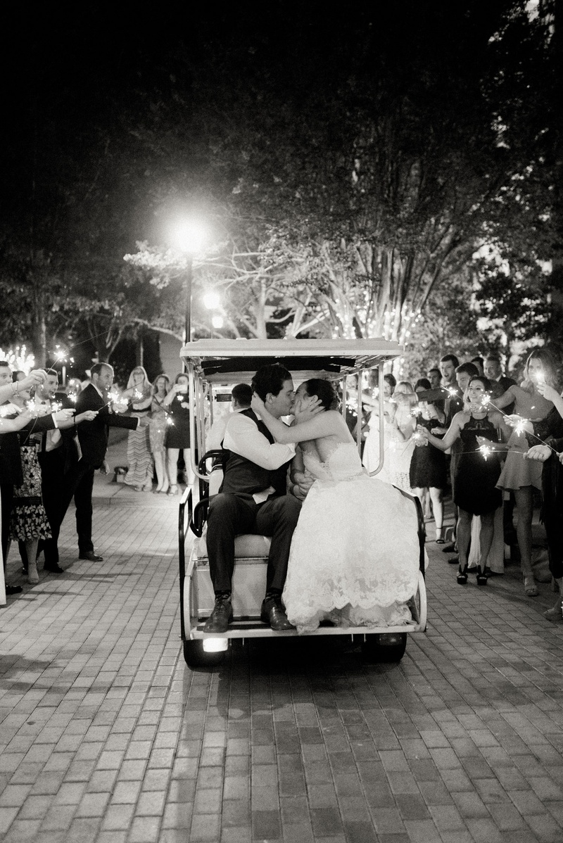 black and white photo of bride and groom on back of golf cart after wedding sparkler exit guests