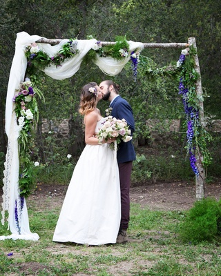 Outdoor wedding ceremony at the Oak Canyon Ranch with a wood arch, white fabric, garlands of flowers