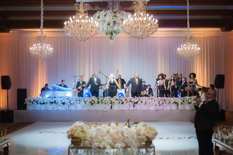 Bonnie Foster Productions at wedding reception dance floor chandeliers white flowers around stage