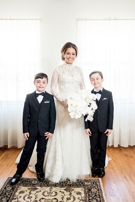 Bride in high neck long sleeve wedding dress orchid bouquet ring bearers in tuxes