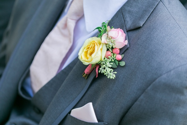 boutonniere with yellow rose, pink tinged white rose, greenery