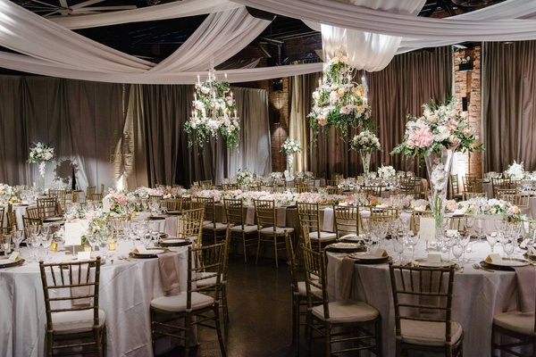 white and gold tablescapes with tall floral arrangements and cascading fabric hanging over space