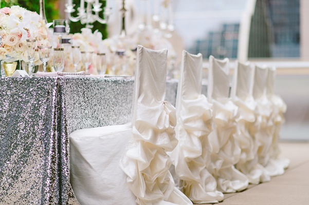 Wedding reception chairs with white chair covers and ruffle skirts