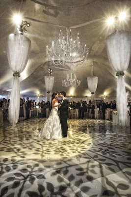 Bride and groom first dance in tent wedding with chandeliers