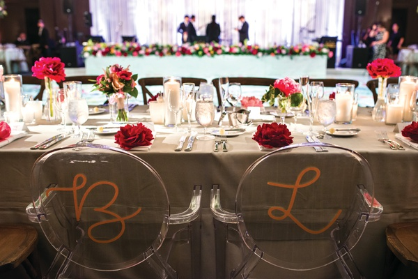 two ghost chairs painted in a gold initial at wedding head table