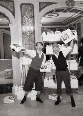 Black and white photo of newsboys passing out special editions of new york times newspapers at end