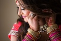 Bride puts on earrings while wearing stacked pink, red, orange bangle bracelets and henna on hands