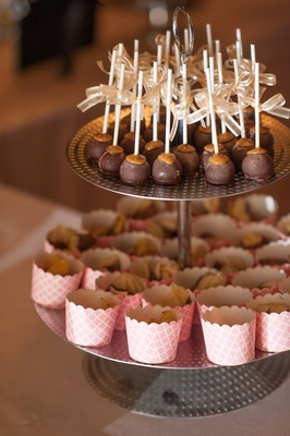 Wedding reception cookie table with cake pops and pink sweets cups on metal stand