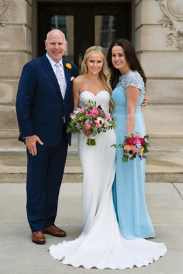 bride in strapless lihi hod bridal gown in between mom in sky blue dress and dad in navy suit