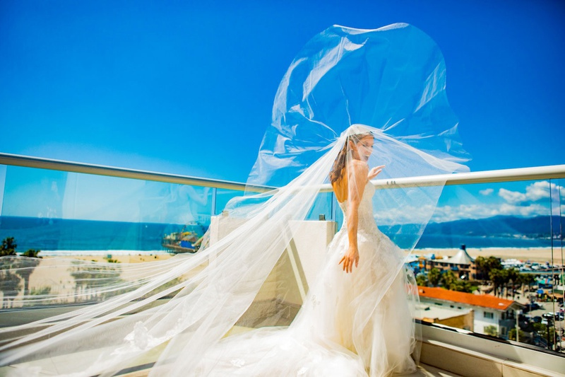 bride in monique lhuillier wedding dress and veil blowing in wind ocean view balcony