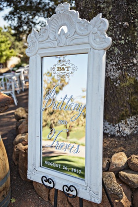 Outdoor wedding welcome sign mirror calligraphy and monogram in distressed white frame on stand