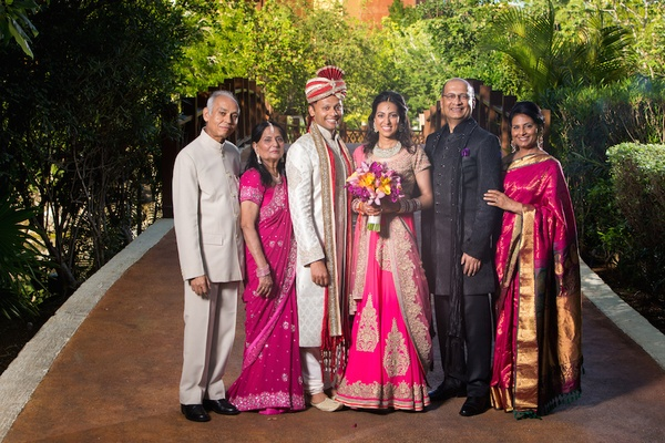 Indian bride in hot pink and gold sari with groom and parents, mothers in fuchsia saris