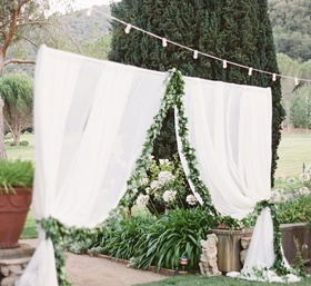 sheer white curtain entrance to outdoor reception space lined with foliage below string of lights