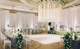 Wedding reception white dance floor chandelier crystal and satin ribbon white flowers greenery