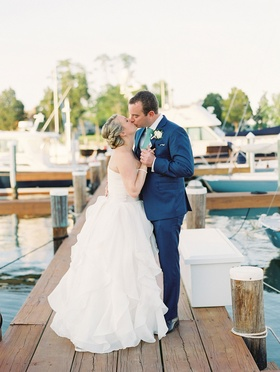 Bride in strapless ball gown kisses groom in navy blue suit and green tie on wood dock wedding venue