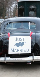 Just Married car with sign tied with red bows and bride and groom kissing in back window