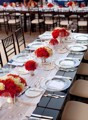 Low centerpieces on white runner reception table