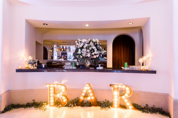 wedding reception after party dancing ballroom flowers on bar with eucalyptus bar letter sign