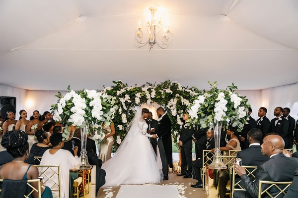 wedding ceremony african american couple tented structure chandelier greenery white orchid flowers