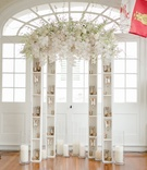 Wedding altar with suspended white orchids, roses, pink roses, curly willow over narrow bookcases