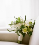 green and white bridal bouquet wrapped with satin white ribbon on armchair