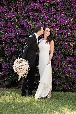 groom going to kiss bride cheek black tuxedo white sheath gown pastel bouquet