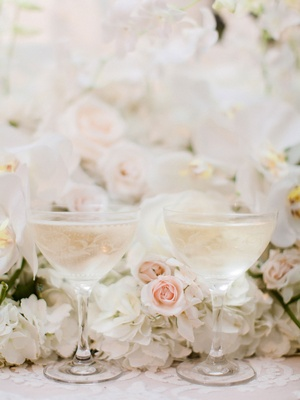 Wedding reception etched coupe glass for champagne at wedding reception with flowers blush ivory